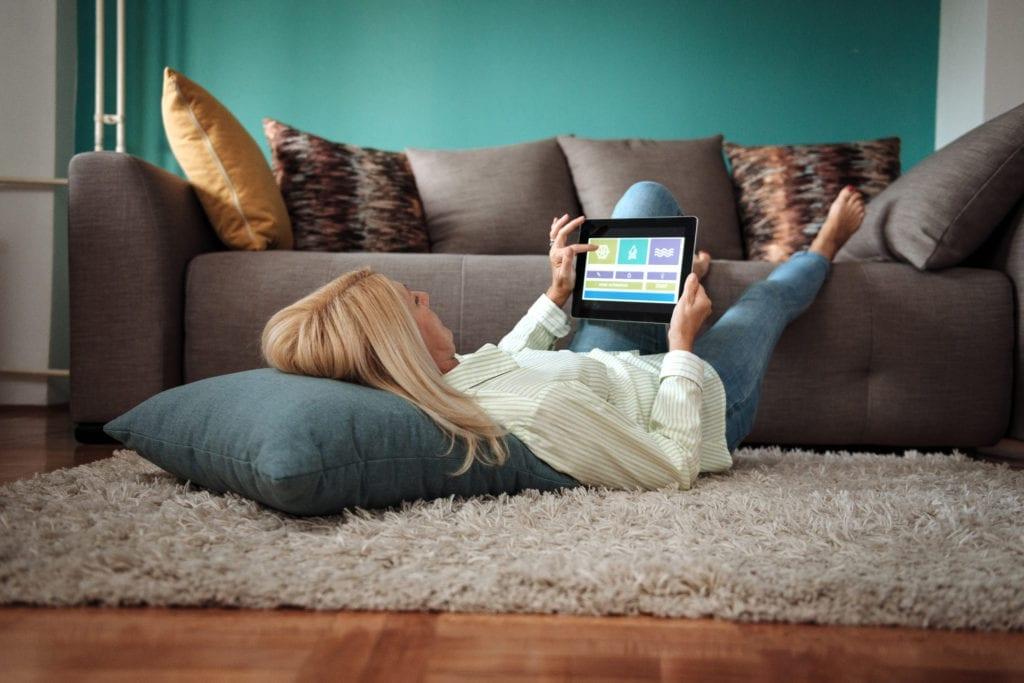 femme alongée qui regarde sa tablette et contrôle les réglages de sa maison