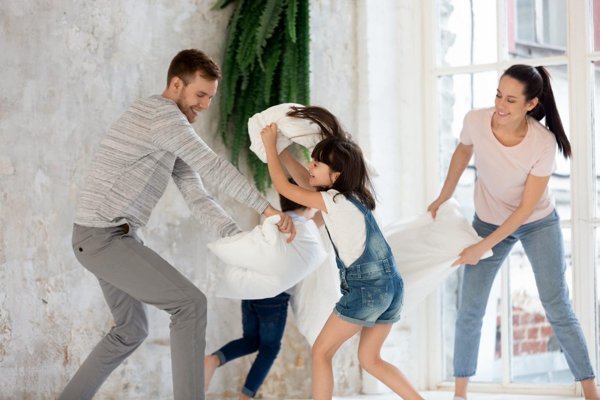 famille qui fait une bataille d'oreillers